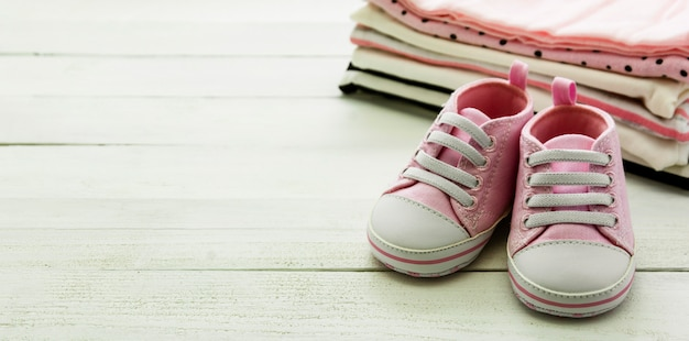 Pink baby girl shoes and newborn clothes. motherhood, education or pregnancy concept with copy space. baner.