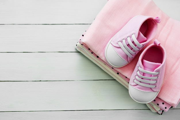 Pink baby girl shoes and newborn clothes. motherhood, education or pregnancy concept with copy space. flat lay.