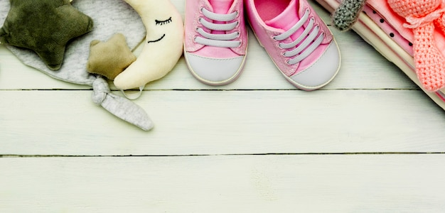 Pink baby girl shoes, newborn clothes and soft toys. motherhood, education or pregnancy concept with copy space. baner.
