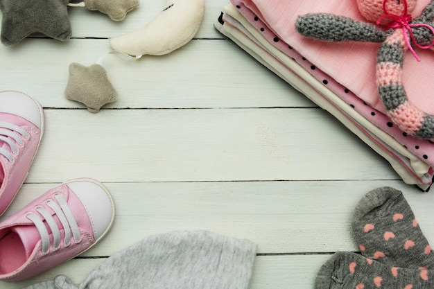 Pink baby girl shoes, newborn clothes and soft toys. motherhood, education or pregnancy concept with copy space.
