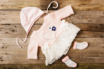 Pink baby's dress with headwear and pair of socks on wooden table