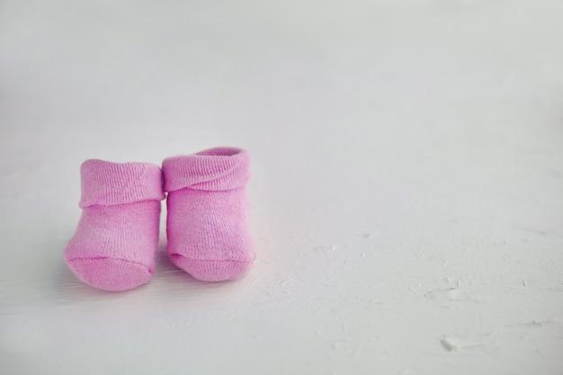 Розовые детские носки на текстурированном деревенском фоне с копией пространства. концепция новорожденных и беременности. маленькая девочка и новая жизнь