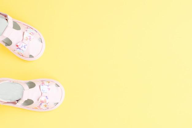 Розовые детские летние сандалии крупным планом на желтом