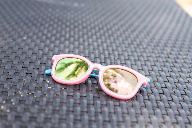 Pink baby sunglasses with palm tree reflection. high quality photo