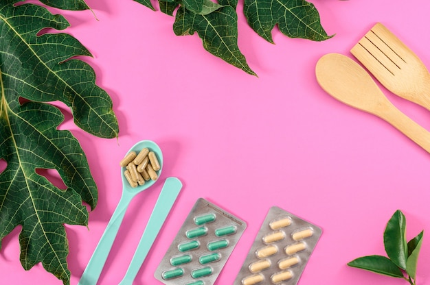 Pink background decoration with dietary supplements with equipment and green leaf. spoon and dietary supplements medicine isolated on pink background.