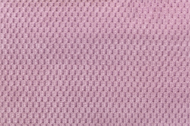 Pink background from soft fleecy fabric closeup. texture of textile macro