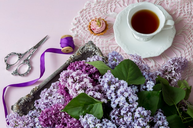 On a pink background a lilac bouquet in an old silver plate