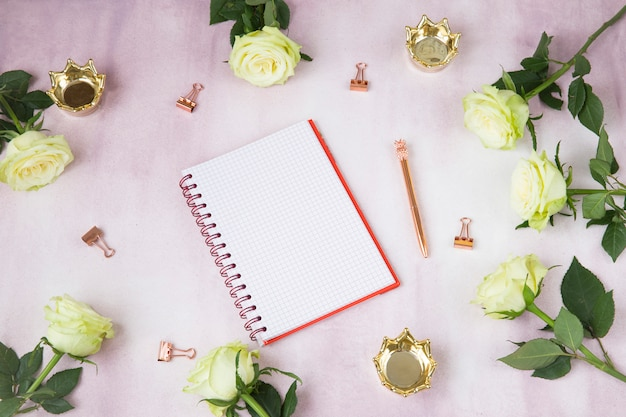 On a pink background notepad, roses, crowns, clips, pen