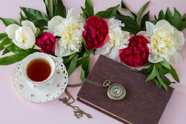 On a pink background peonies, a cup of tea, a book and a pocket watch