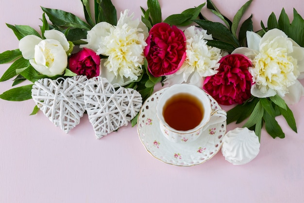 On a pink background peonies, a cup of tea, two white hearts and marshmallows