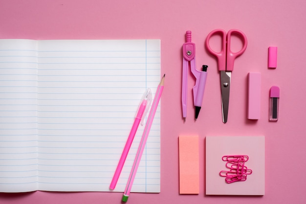 On a pink background, school accessories and a pen, colored pencils, a pair of compasses, a pair of compasses, copyspace, top view
