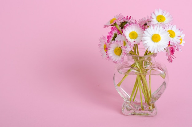 Pink background for valentines day card, vase with flowers in shape of heart.