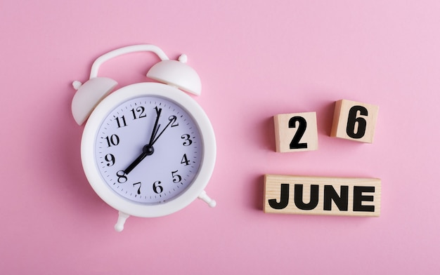 On a pink background, a white alarm clock and wooden cubes with the date of june 26