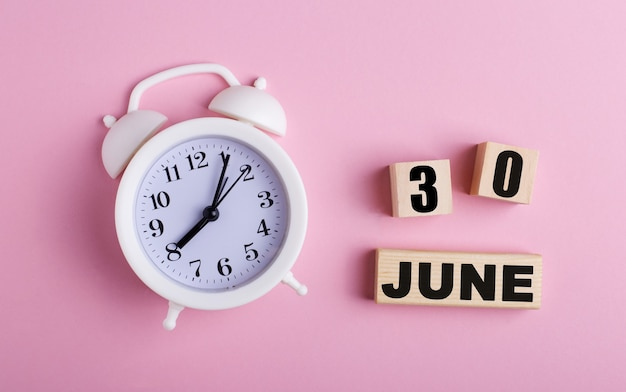 On a pink background, a white alarm clock and wooden cubes with the date of june 30