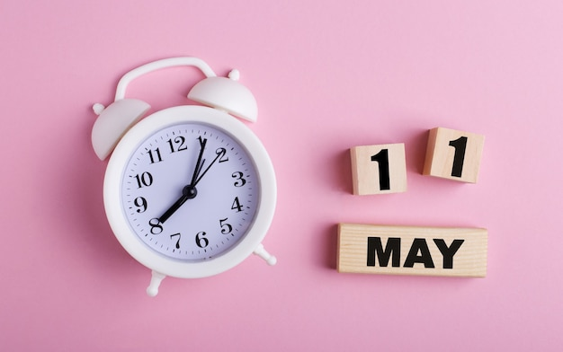 On a pink background, a white alarm clock and wooden cubes with the date of may 11