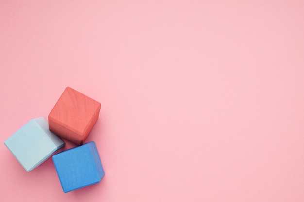Pink background with colorful wooden cubes. creativity toys. children's building blocks.