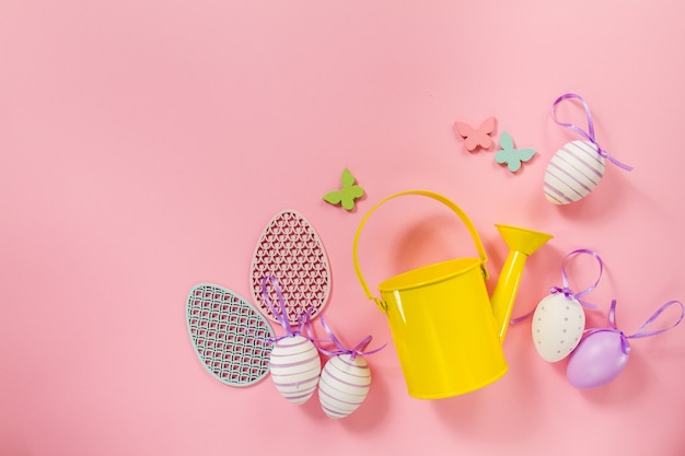 Pink background with easter eggs and yellow watering can