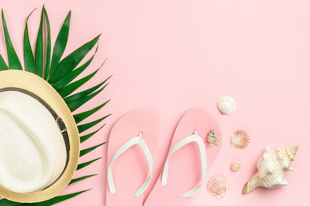 ピンクの背景にフリップフ ロップ、帽子、貝殻。夏の販売コンセプト。