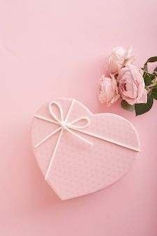 Pink background with flowers and gift box