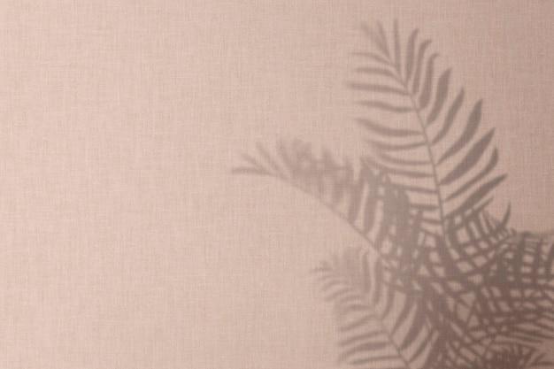 手のひらの葉の影とピンクの背景