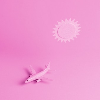 Pink background with plane and sun