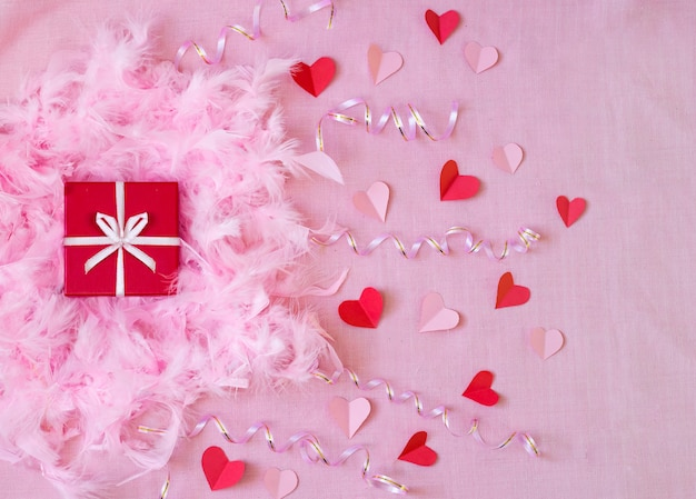 Pink background with red present and paper hearts