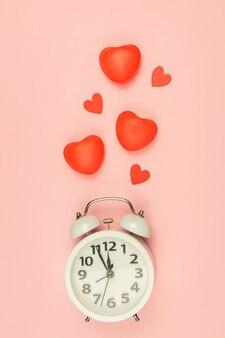 白い目覚まし時計と赤いハートとピンクの背景。クリエイティブなレイアウト。上面図。