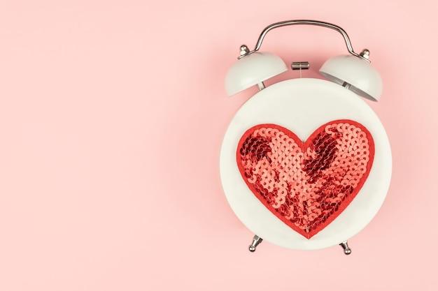 赤いスパンコールの心と白い目覚まし時計とピンクの背景。クリエイティブなレイアウト。上面図。