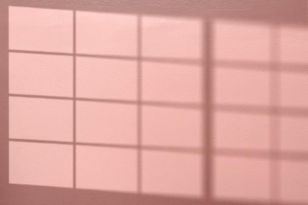 Sfondo rosa con ombra della finestra riflessa sul muro