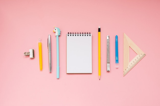 Pink background and yellow school supplies