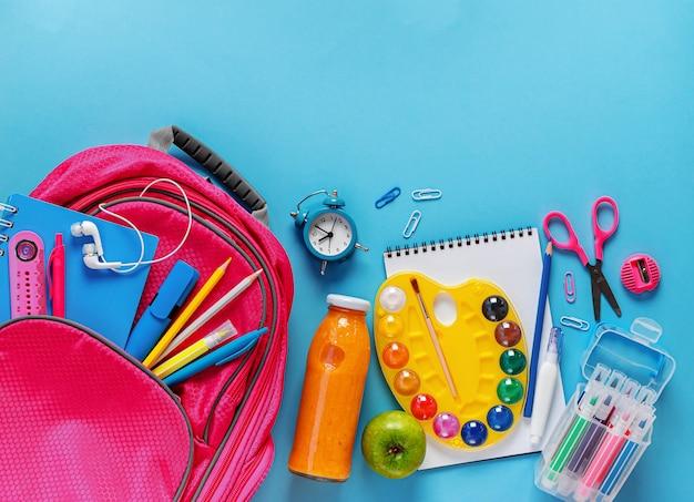 Розовый рюкзак, бутылка фруктового смузи и канцелярские товары на синем фоне.