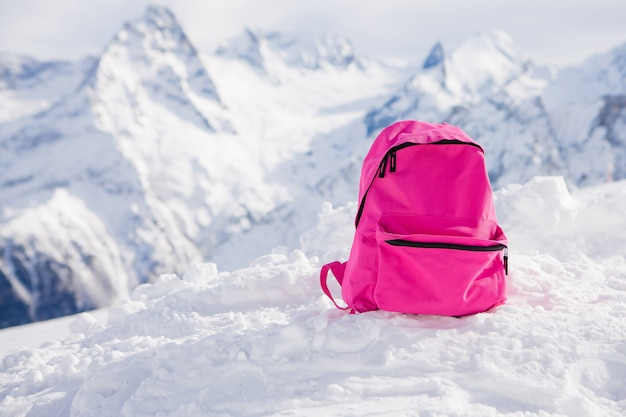 Pink backpack in the of snowy mountains.
