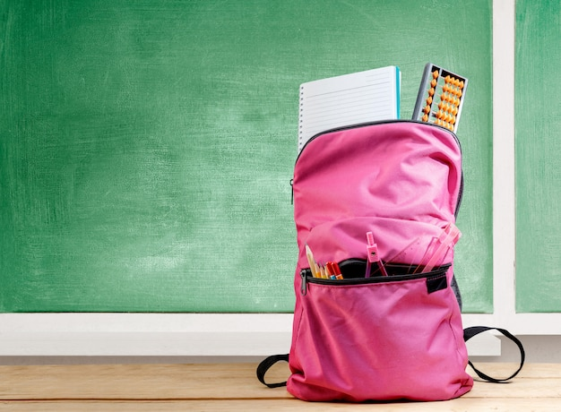 Pink backpack with book and different stationery on the wooden table