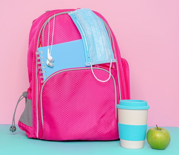 Pink backpack with medical mask, reusable eco cup and apple.