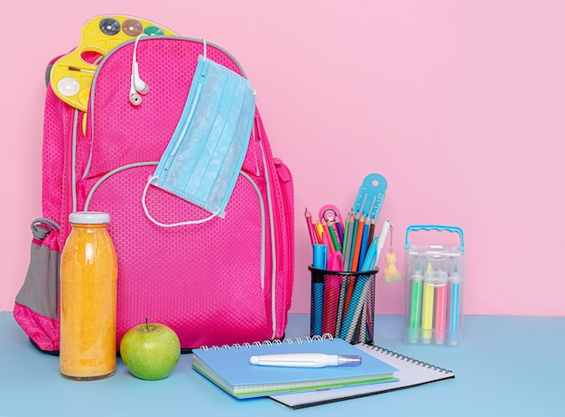 Pink backpack with medical mask, school supplies and lunch of fruit smoothie and apple