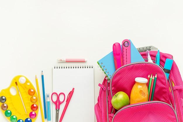 Розовый рюкзак со школьными принадлежностями и обедом на белом фоне. вид сверху, копия пространства.