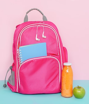 Pink backpack with snack of fruit smoothie bottle and apple
