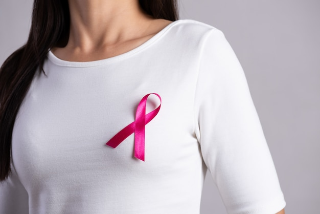 Pink badge ribbon on woman chest to support breast cancer cause. healthcare concept.