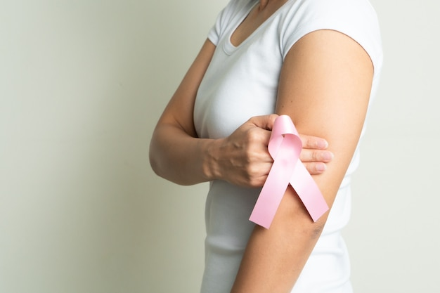 Pink badge ribbon on woman hand touching chest to support breast cancer cause. breast cancer awareness concept