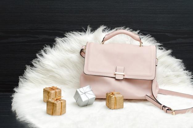 白い毛皮、黒いテーブルにピンクのバッグとギフトボックス。ファッショナブルなコンセプト