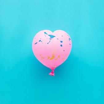 青いパーティーのお祝いにピンクの風船のハートの形