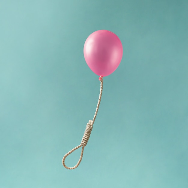 Розовый шар с петлей палача на синей поверхности