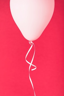 Pink balloon with ribbon on red background