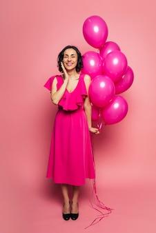 Розовые воздушные шары. фотография в полный рост счастливой девушки в длинном платье цвета фуксии, которая улыбается с закрытыми глазами и держит в левой руке розовые воздушные шары.