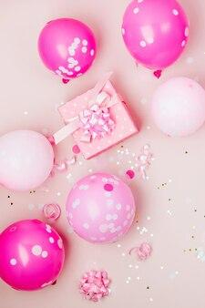 Розовые воздушные шары, подарок с конфетти, бантики и бумажные украшения. тема концепции вечеринки по случаю дня рождения. плоская планировка, вид сверху