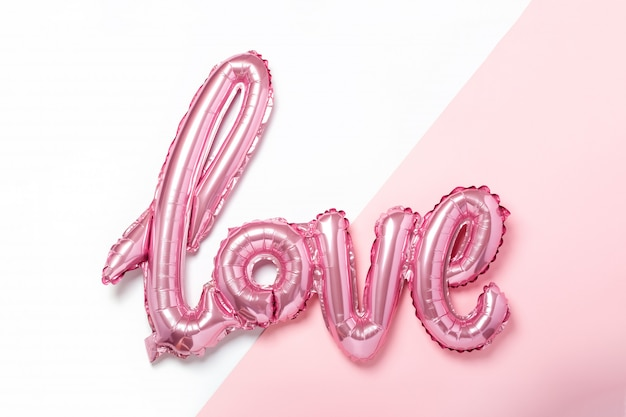 Розовые воздушные шарики в виде слова love на розово-белом цвете