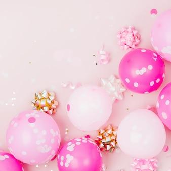 Розовые шары с конфетти, бантами и бумажными украшениями. тема концепции вечеринки по случаю дня рождения. плоская планировка, вид сверху