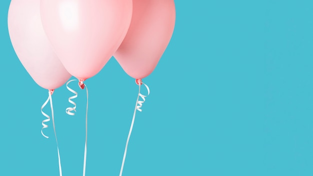 Pink balloons with ribbons on blue background