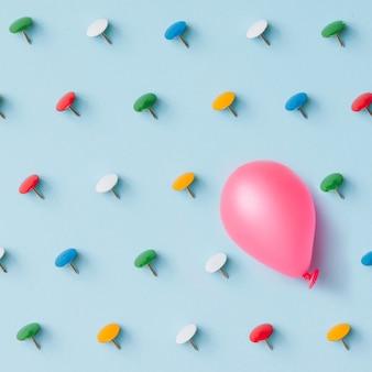 파란 벽에 화려한 핀 핑크 baloon입니다. 역경 또는 독특한 개념. 평평하다. 평면도.