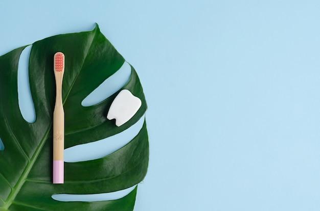 Розовая бамбуковая зубная щетка на листе монстера с копией пространства